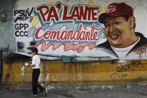 A child walks past a mural depicting Venezuela's President Chavez in Caracas