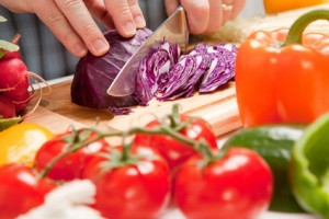 Man Slicing Vegetables on Wooden Cutting Board.