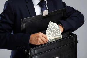 Business man hiding money in briefcase on gray background