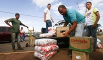 Men load boxes of food onto the back of a pick-up truck, after arriving from Brazil, in front of the bus terminal in Santa Elena de Uairen