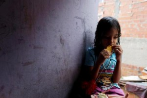 One of Yennifer Padron and Victor Cordova's daughters eats an arepa in the family room of the house that they share at Petare slum in Caracas