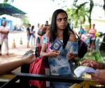 A Venezuelan woman shows her passport and identity card at the Pacaraima border control, Roraima state